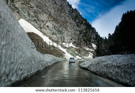 A Car passes through a road as it was cleared of snow in sonamarg , Kashmir India