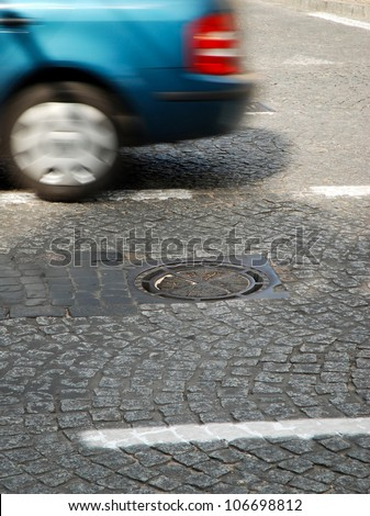 a car passing manhole cover on a paved road #106698812