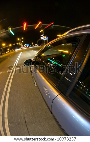 A car, reaching stand-still for the red lights of a traffic light at night