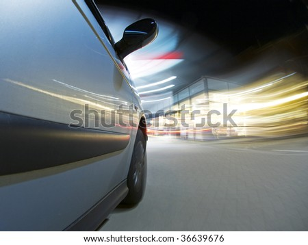 A car, running on empty, driving into a petrol station at night to get refueled