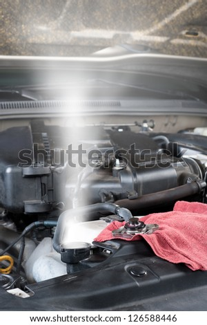 A car's overheated radiator shoots out hot steam.