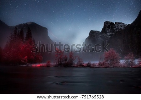 A car's tail lights paint  trees red at night in Yosemite at the Gates of the Valley under a starry sky, fresh snow . A fog obscures El Capitan and Cathedral Rock with its beautiful Bridalveil Falls.