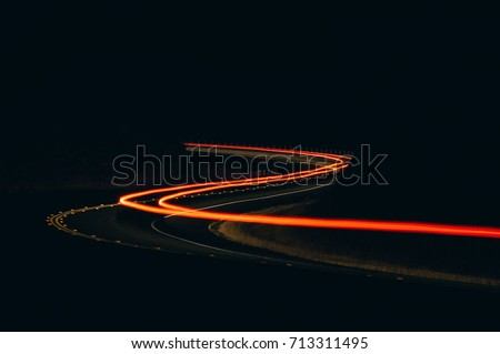 A car's taillights weave across a rural highway in Sonora, California.