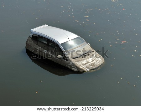 A Car Sits in a Flooded Car Park - Motor Vehicle Insurance Claim Themed Image #213225034