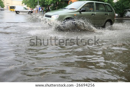 A car splashes through a large puddle on a wet road.