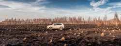 A car standing in the field of burnt out grass