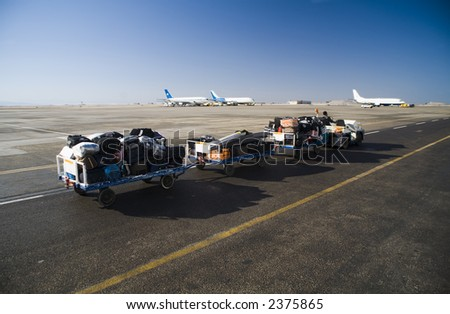 a car takes away luggage of the air passengers to the plane