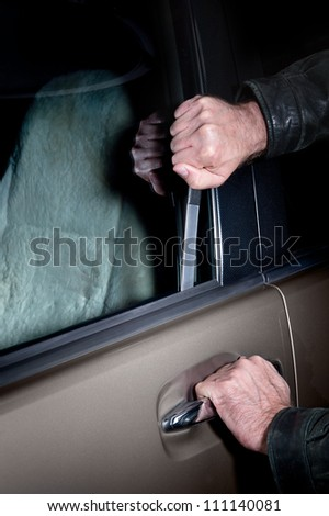 A car thief uses a Slim Jim tool to pop the lock on a car door to steal it.