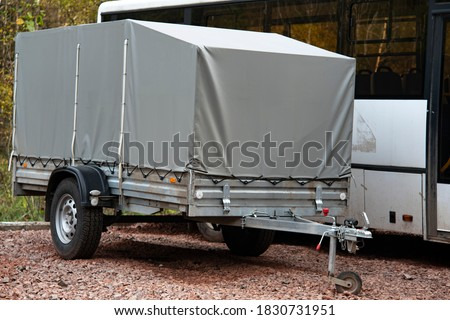 A car trailer covered with a gray tarpaulin in an unpaved parking lot. Сток-фото ©