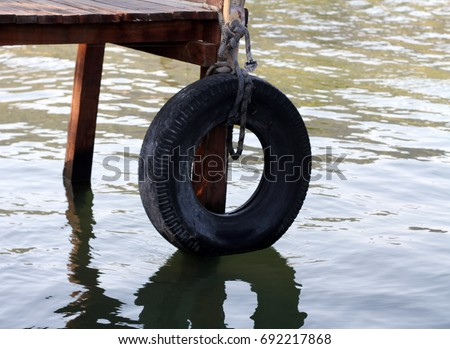 a car tyre hanging on the deck to the sea Stok fotoğraf ©