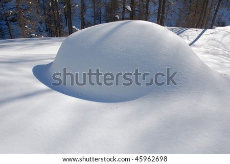 A car under a pile of snow after a very heavy snowfall