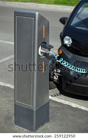 A car with power supply is connected to a column through a charging cable that transmits electricity to the internal battery.