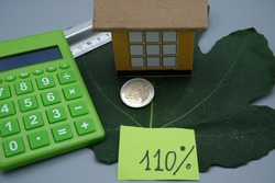 A cardboard house, on top of a fig leaf, with a coin, a calculator, and a ruler, with one hundred and ten percent written on it. Facilitation concept for renovations