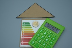 A cardboard triangle, with an energy saving table with a coin, next to a calculator, with written bonus. Tax relief concept