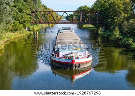 a cargo canal ship passes under an old iron bridge on a sunny autumn day, reflections are to be seen in the water, canal system in the outskirts of Berlin Germany Foto stock ©