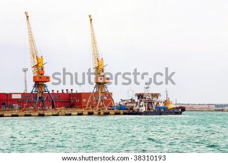 A cargo port works. Huge cranes on a pier.