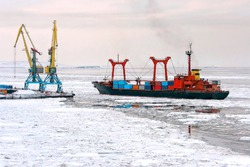 A cargo ship with containers near the pier of the seaport. Maritime navigation and shipping in the Arctic. The ship passes among the ice floes. Anadyr Sea Port, Chukotka, Far East Russia. November.