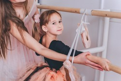 A caring mother and her little daughter are doing ballet. The trainer teaches a little girl ballet. Sport and gymnastics concept. Two ballerinas. A little girl in a pink skirt is engaged in art.