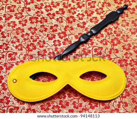 a carnival mask with handle on a patterned background