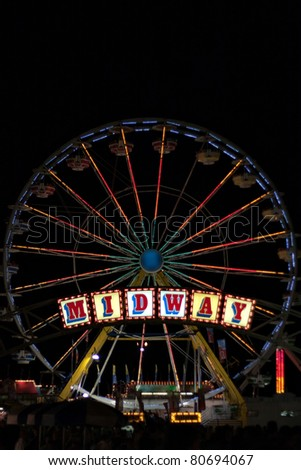 A carnival or fair midway with a large ferris wheel lit up with many lights.