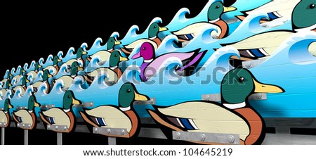 A carnival shooting alley mechanism with a wooden purple toned mallard duck swimming against the flow of the other ordinary mallard ducks in between wave cutouts