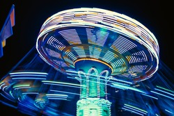 A carousel with bright lights of different colors in a rotary motion