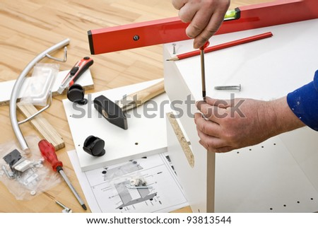 A carpenter builds a small white cabinet with a screwdriver together on a parquet floor. - stock photo