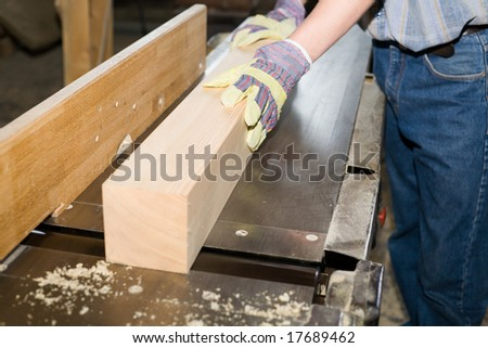 A carpenter(sawman)  works on woodworking the machine tool.