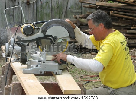 A carpenter using a chop saw