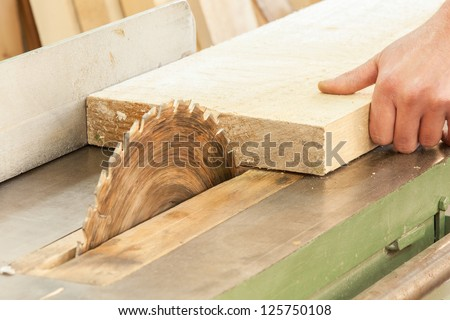 A carpenter  works on woodworking the machine tool. Carpenter working on woodworking machines in carpentry shop.