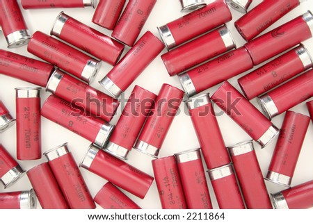 A carpet of 12 guage shotgun shells lying on a white background.