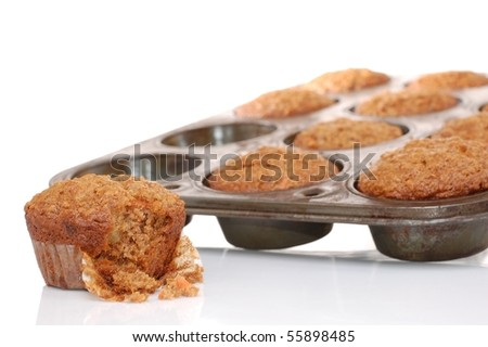 A Carrot Muffin with a Bite Taken Out of it with a Muffin Tin in the Background