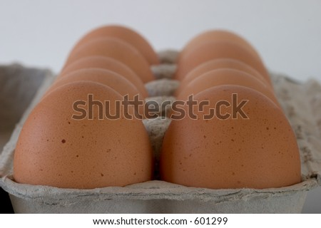 A carton of brown eggs, viewed from one end, close-up, shallow depth of field.