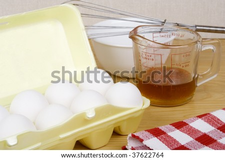 A carton of eggs, a bowl, a whisk and some maple syrup, ready to be mixed.