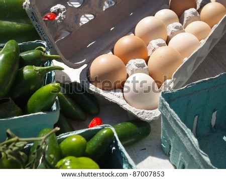 A carton of fresh brown eggs for sale on a farmer's market table.