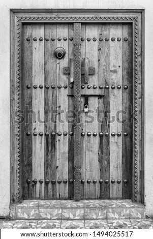 A carved wooden door  at the entrance to a restored traditional arabian house.carved wooden door  at the entrance to a restored traditional arabian house.