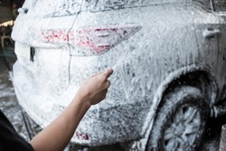 A carwash employee using a high pressure hose to cover large SUV with shampoo to loosen the grime and dirt.