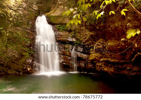a cascade on rock falling into lake
