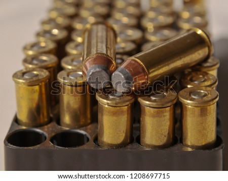 A case of .44 magnum bullets lined up with two of them removed and laying on top of the others