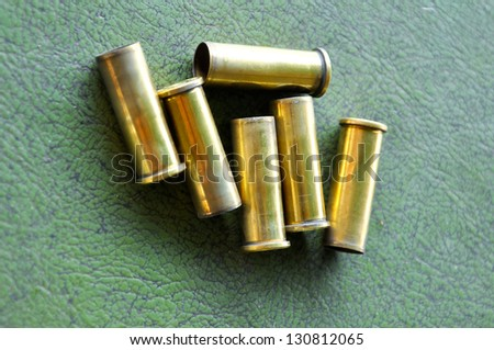 a casing containing a charge and a bullet or shot for small arms or an explosive charge for blasting.