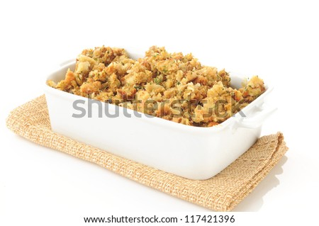 A casserole dish of herb stuffing in turkey broth on a white background