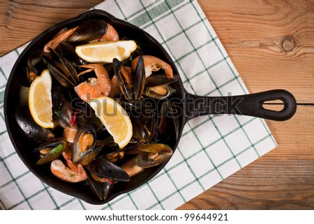 A cast-iron pan filled with delicious mussels and prawns garnished with fresh lemon. Rustic mussels and prawns.