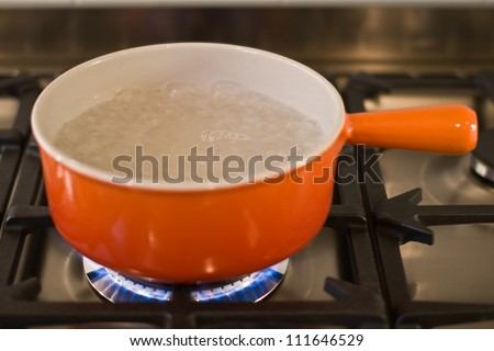 A cast iron pan of boiling water on a modern gas range cooker