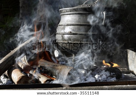 A cast iron pot is used for traditional cooking on an open for Fire pots south africa