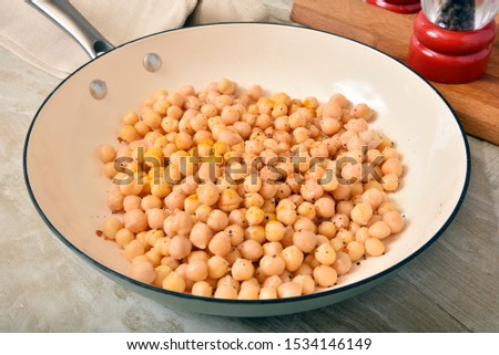 A cast iron skillet with seasoned garbanzo beans to be fried