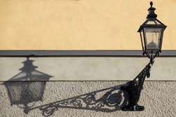 A cast iron street lamp on a yellow and gray plastered wall in daylight with a clear shadow on the wall. Bright sunlight, patterned lantern bracket.