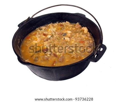 a caste iron pot of seafood gumbo on a white background