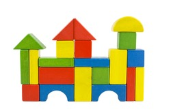 A castle house - castle created of colorful wooden toy blocs in red, yellow, green and blue, isolated on white.