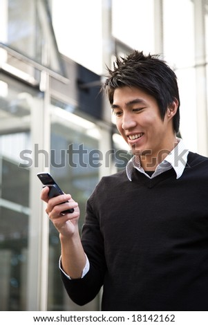 A casual asian businessman texting messages on his cellphone