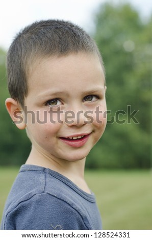 A casual close up summer outdoor portrait of a happy small child boy.